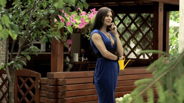 Elegant brunette talks on phone standing near summer house video