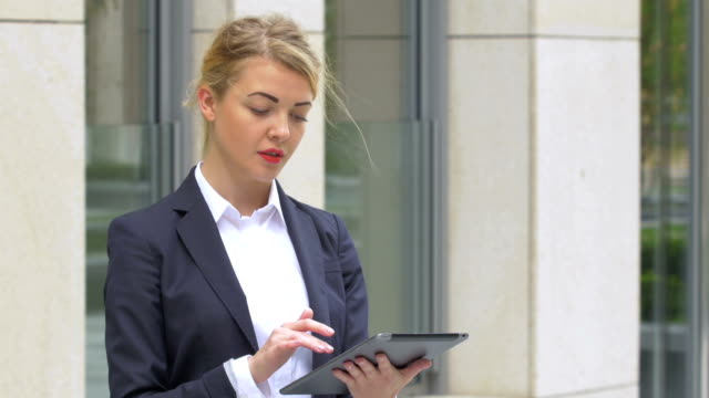 elegant business woman with tablet computer near office building. close up video