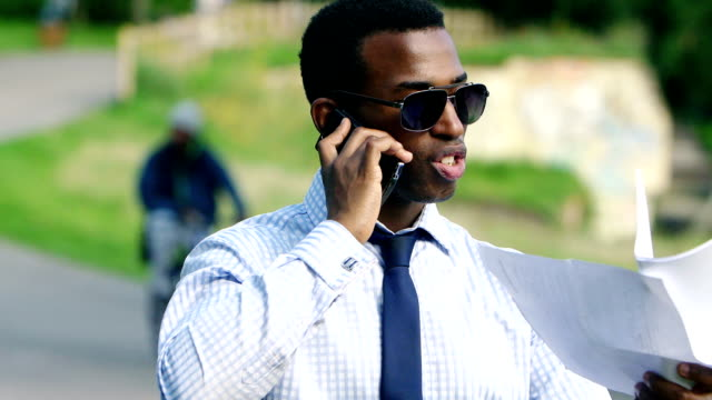 elegant businessman arguing at the phone in the park video