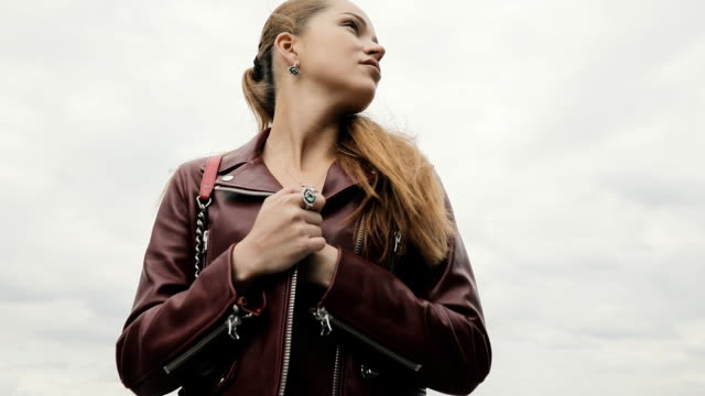 Elegant woman in burgundy leather jacket against cloudy sky, slowmotion video