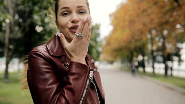 Elegant woman in burgundy leather jacket make aerial kiss walking in city street, slowmotion video