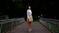 Elegant woman stand on footbridge and turn back with hurt emotion, slow motion video