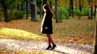 Elegant woman wait someone at autumn park, bright autumn leaves video