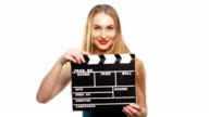 Elegant woman with sexy red lips go, using clapper board and smiling, on white video
