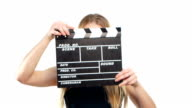 Elegant woman with sexy red lips using clapper board and smiling, on white video