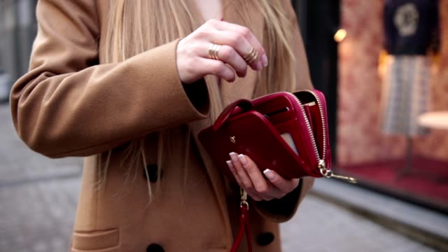 Elegant woman's hand opening red purse outdoors video