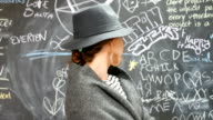 Elegant young woman standing in front of a black board filled with scribbles and looking at camera video
