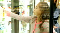 Elementary age child helps Caucasian mid-adult mother shop in the dairy section of local supermarket video