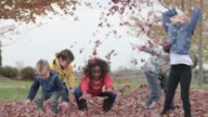 Elementary Children Throw Autumn Leaves in the Air video