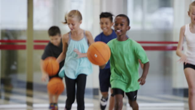 Elementary kids playing basketball during physical education class video