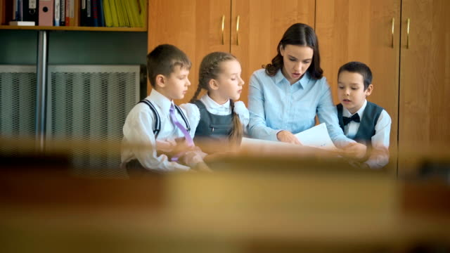 Elementary school pupil and teacher discussing picture with classmates video