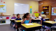 Elementary school students raise hands in classroom video