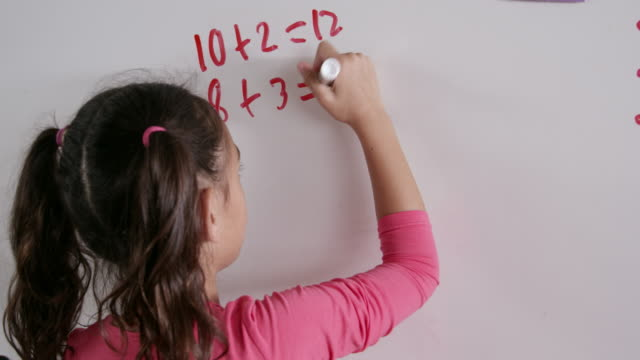 Elementary schoolgirl doing maths on whiteboard, back view video