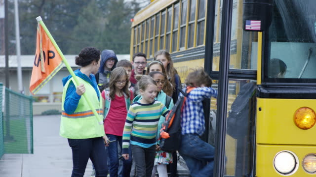 Elementary students getting onto schoolbus video