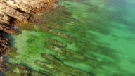 Emerald ocean wave on a rocky beach aerial view video