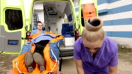 Emergency medical ambulance service paramedics crew fixing senior patient on stretcher video
