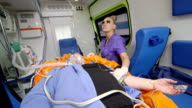 Emergency medical technician provide critical care to patient in ambulance video