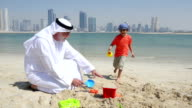 Emirati grandfather and little boy playing on the beach video