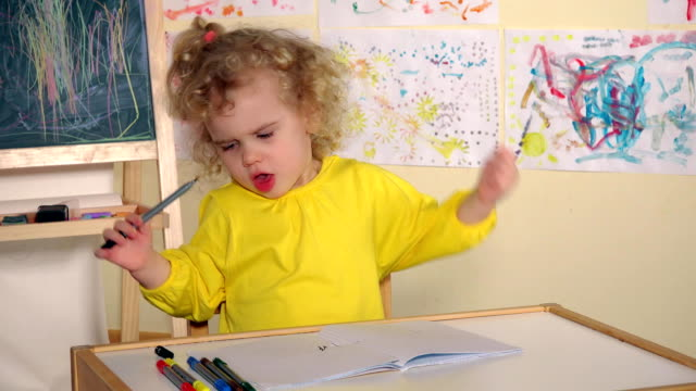 Emotional blonde girl child draw with pencil in book on table video