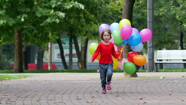 emotional girl runs with multicolored balloons, Slow motion video