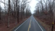 Empty back country road on cloudy day flyover video