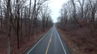 Empty back country road on cloudy day pull back video