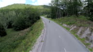 Empty forest road with longboard skaters ride through video