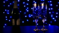 empty glasses and bottle of champagne on the blue boke background video