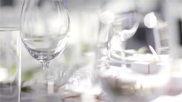 Empty glasses for wine and water set on a festive table in a restaurant – focus shift of glassware. Table decoration video