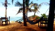 Empty hammock waving in wind at beach resort, stormy day, off-season, crisis video