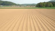 AERIAL: Empty plowed soil lines on agrarian field prepared for crop planting video