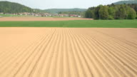 AERIAL: Empty plowed soil lines on farm field prepared for harvest planting video