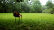 Empty wooden swing swaying slowly in the rain video
