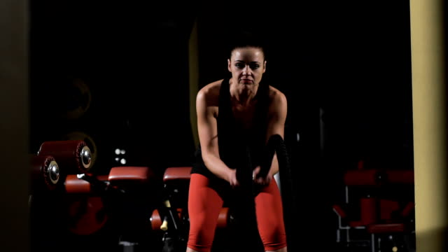 Endurance. Muscular woman exercising with rope in cross traininggym video