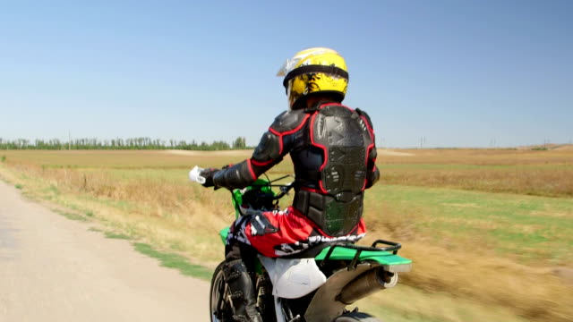 Enduro racer in motorcycle protective gear riding bike video