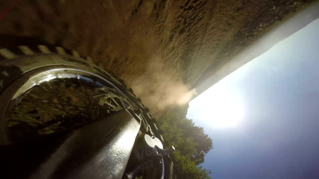Enduro racer riding bike on dirt track kicking up dust rear wheel point of view video