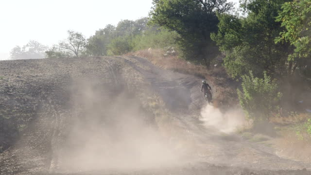 Enduro racer riding motorcycle on dirt track kicking up dust video