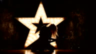 energic and sexy blonde woman wearing leather jacket and playing a guitar, shining star in the background, slow motion, silhouette video