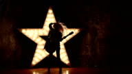 energic woman wearing leather jacket and playing a guitar, shining star in the background, slow motion, silhouette video