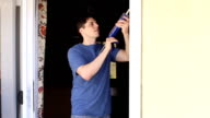 Energy Efficiency Man Caulks Door Blue Shirt video