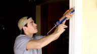 Energy Efficiency Man Caulks Door video