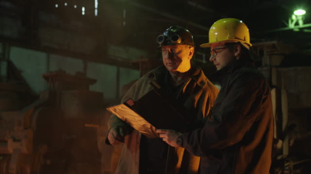 Engineer and Worker Have Conversation in Foundry. Rough Industrial Environment. Middle Shot. video