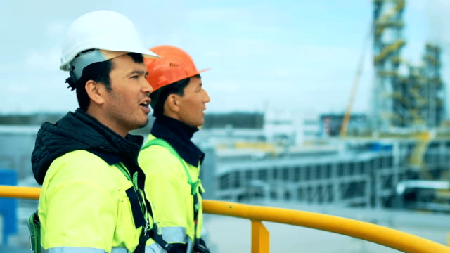Engineer and worker of oil refinery are standing on the tower video