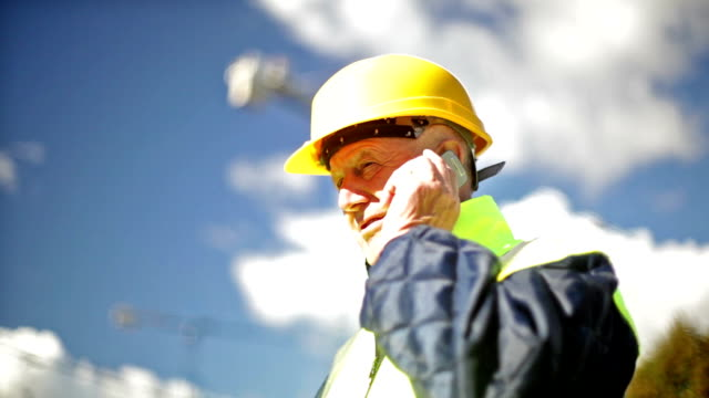 engineer at a construction site talking on the phone. video