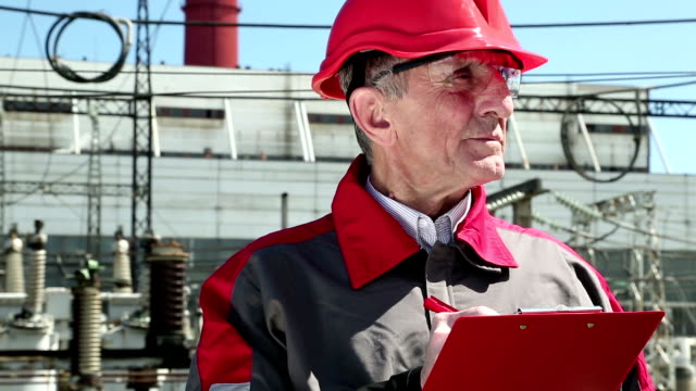 Engineer builder in red helmet writes down information about object video