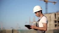 Engineer builder using tablet and walkie talkie video