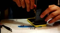engineer check new display on smartphone, during cellphone repair video