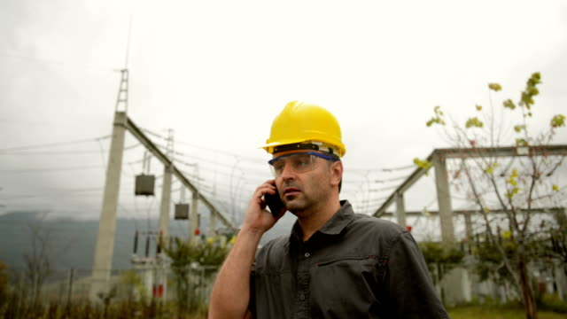 Engineer in front power station using phone video