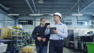 Engineer in Hard Hat and Factory Worker are Walking through Production Facility video