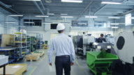 Engineer in Hard Hat is Walking through Factory and Greeting a Worker video